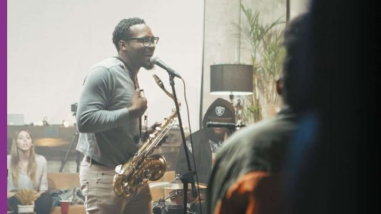 Josue Simon singing with saxophone