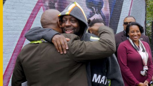 wyclef jean hugging a man, wyclef mural, wyclef, newark, upgraded, ras baraka